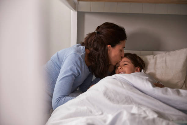 Mother Kissing Goodnight To Daughter At Bedtime stock photo
