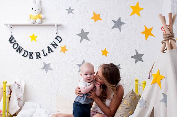 mutter, küssen ihr baby junge vor der schlafenszeit - tipi bett stock-fotos und bilder