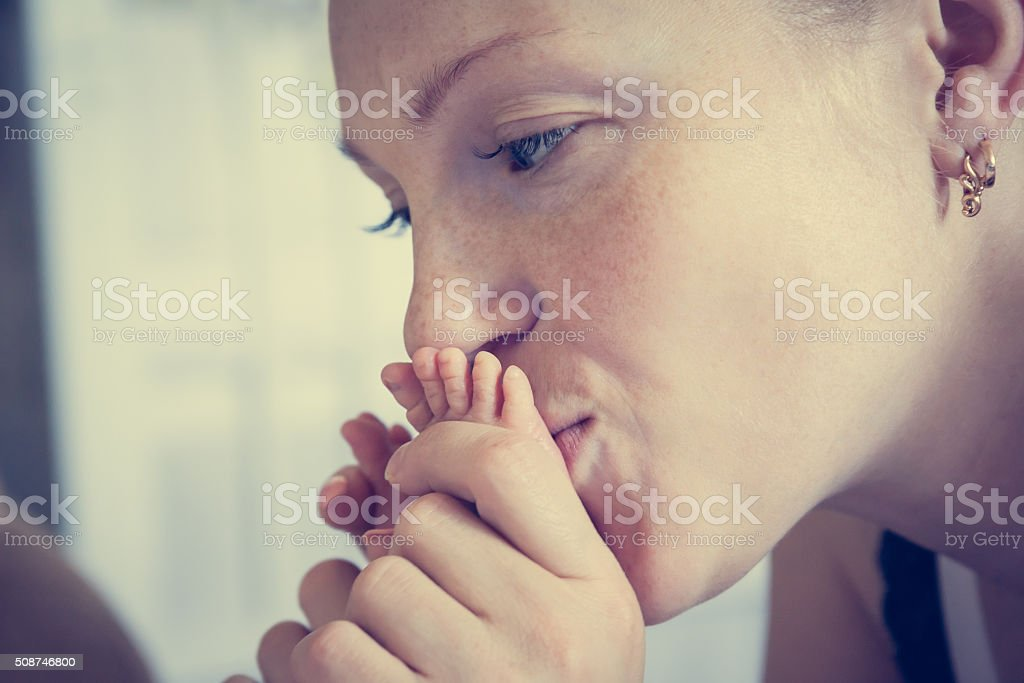 Mother kissing her baby feet symbolizing tenderness and care stock photo