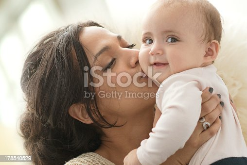 Mother holding and kissing baby girl