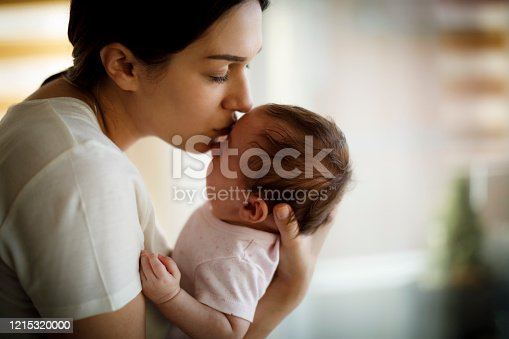 Mother kissing her crying baby