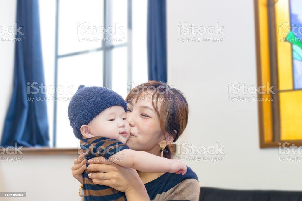 母は彼女のかわいい赤ちゃんの男の子にキス ストックフォト