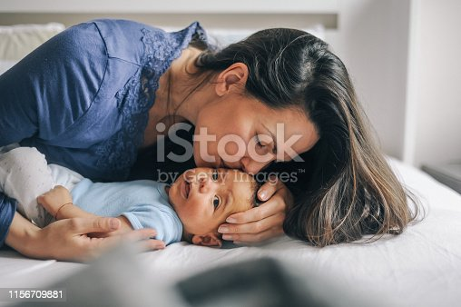 Mother kissing  her newborn baby boy at. They are lying in bed