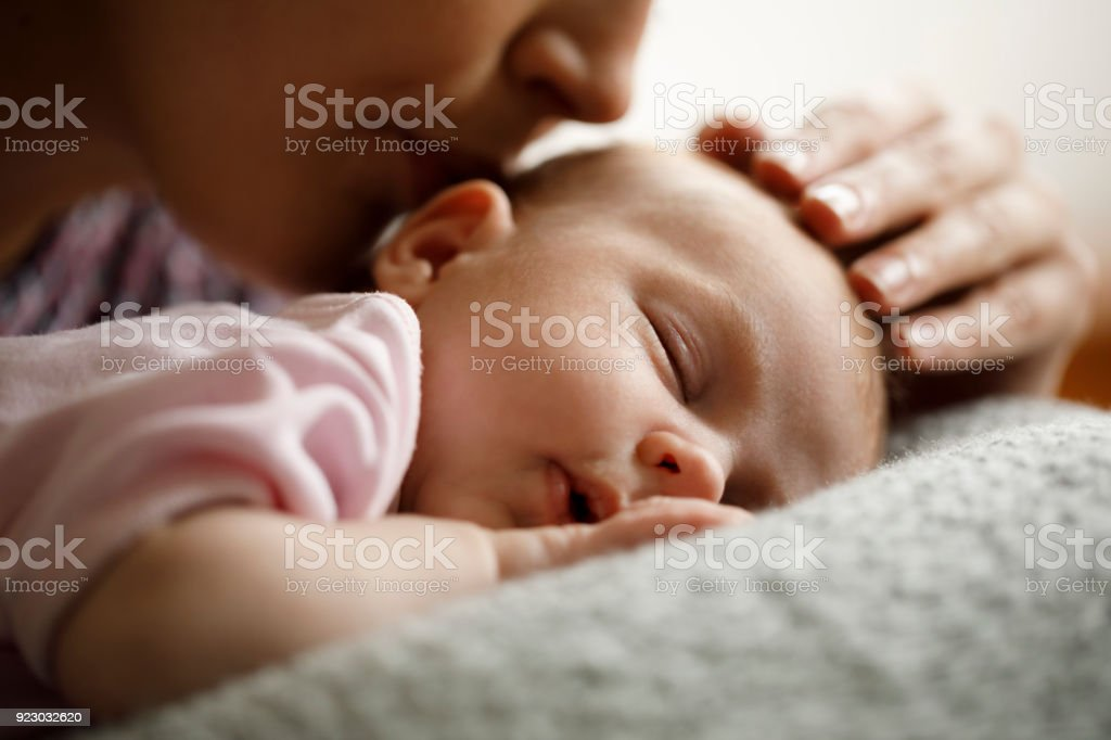 Mother kissing her sleeping baby stock photo