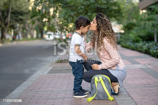 Beautiful picture of a mother kissing her son goodbye while taking him to school - lifestyle concepts