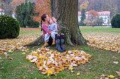 istock Mother kissing little son outside near heart shape of leaves 917866508