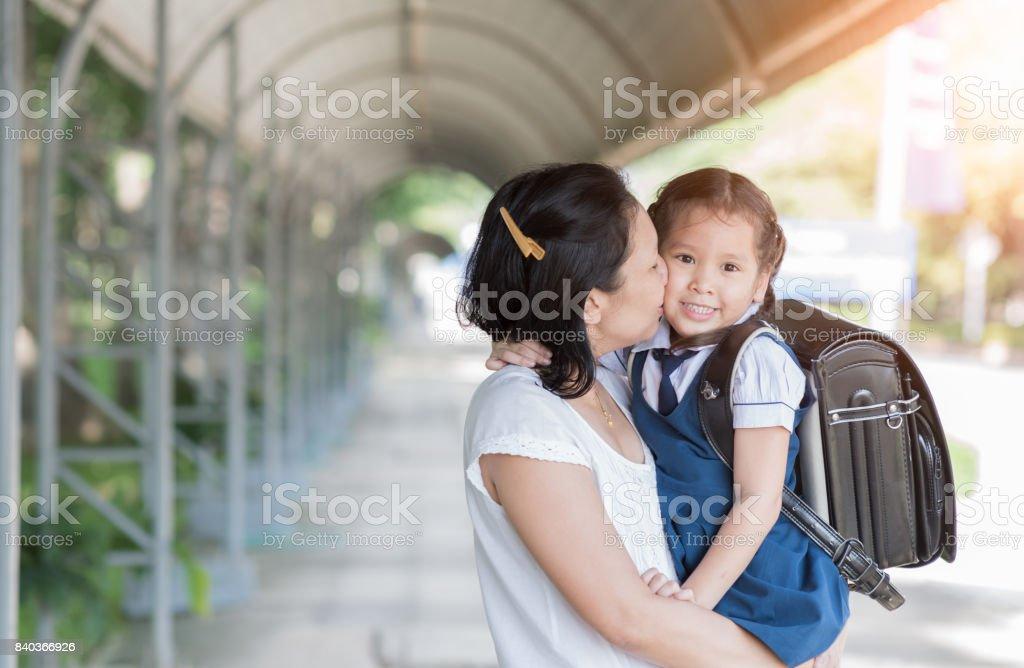 Mother kissing schoolgirl in uniform. stock photo