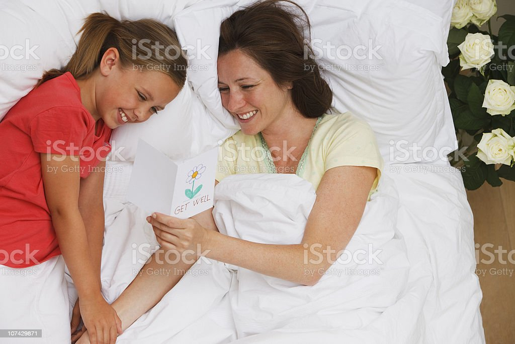 Mother laying in bed reading daughters get well card royalty-free stock photo