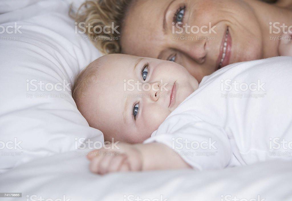 Mãe pôr na cama criança sorridente foto de stock royalty-free