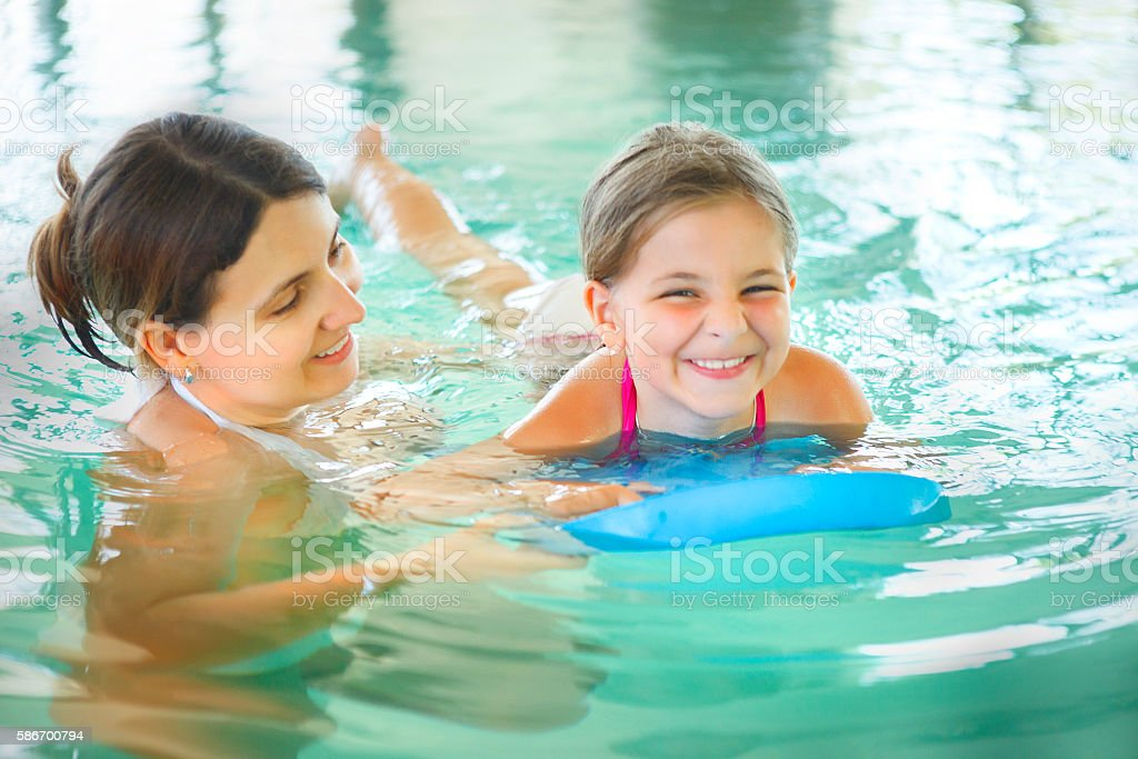 Mother learning to swim her little daughter indoor swimming pool stock photo
