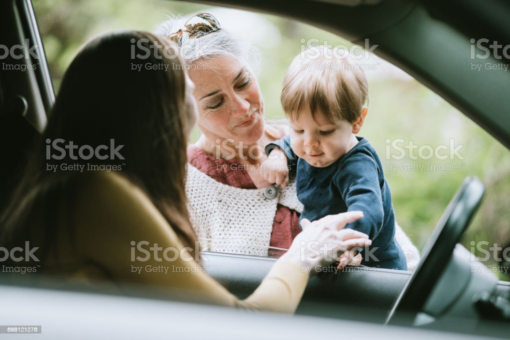 Mother Leaving Child with Grandmother stock photo