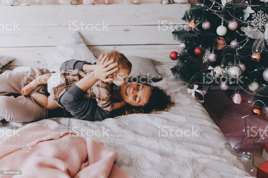 Mother lies on a bed with daughter. stock photo