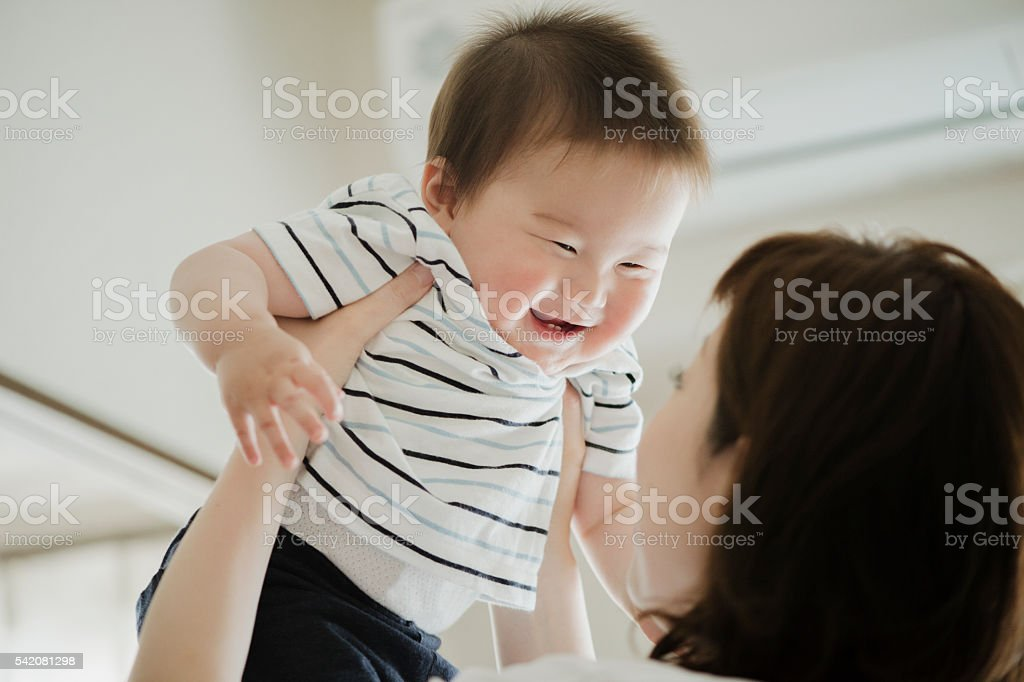 Mother lifting a smiling baby. stock photo