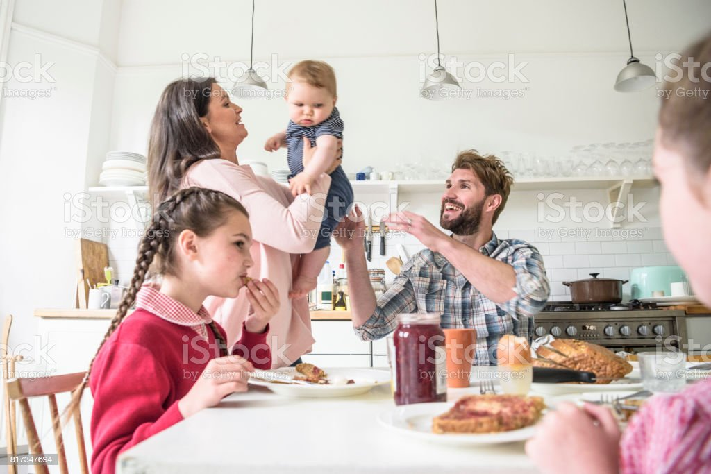 Mother lifting baby son and passing over to father, girls eating breakfast stock photo