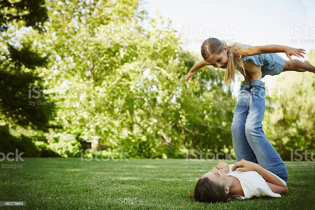 Mother lifting daughter with legs in park stock photo