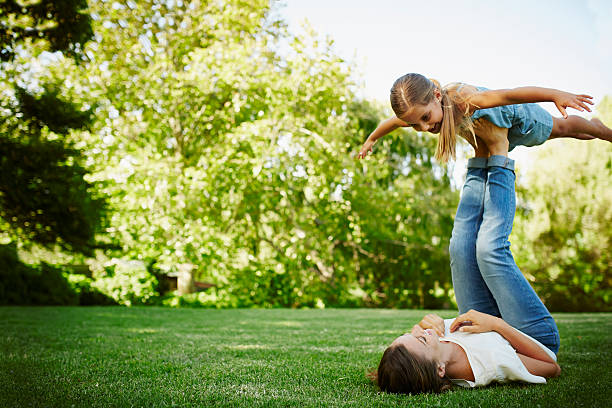 mother lifting daughter with legs in park - kinderjeans stock-fotos und bilder