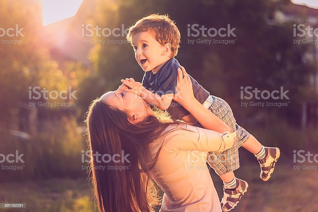 Mother lifting her son up stock photo