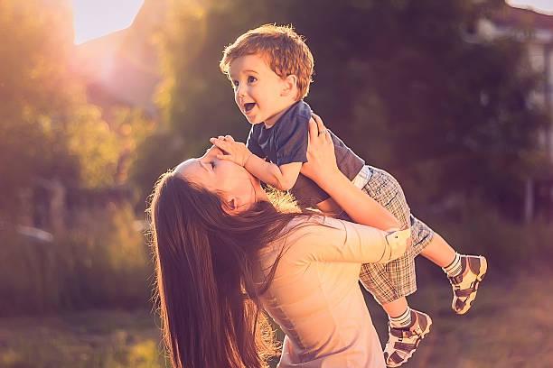 Madre con su hijo arriba de elevación - foto de stock