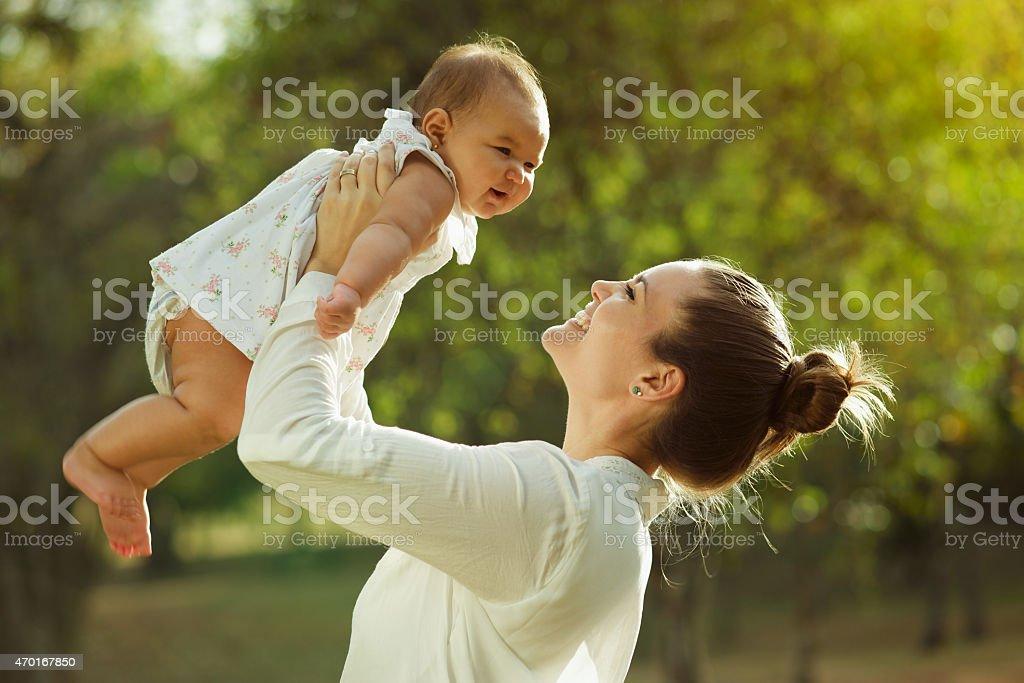 Mère levant vous tournant autour de Little sa petite fille dans le parc - Photo