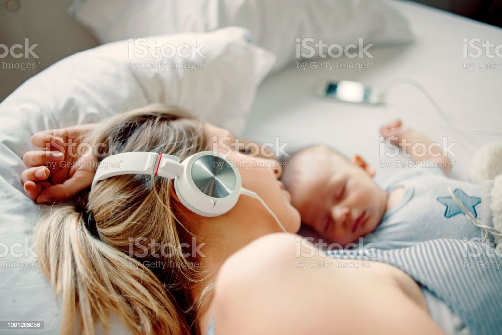 mother listening to music and napping with her baby stock photo