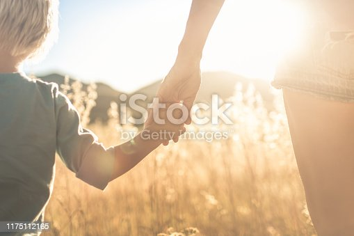 Mother and son holding hands walking at sunset.