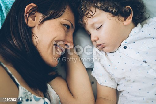 Affectionate mother smiling while looking at her toddler sleeping
