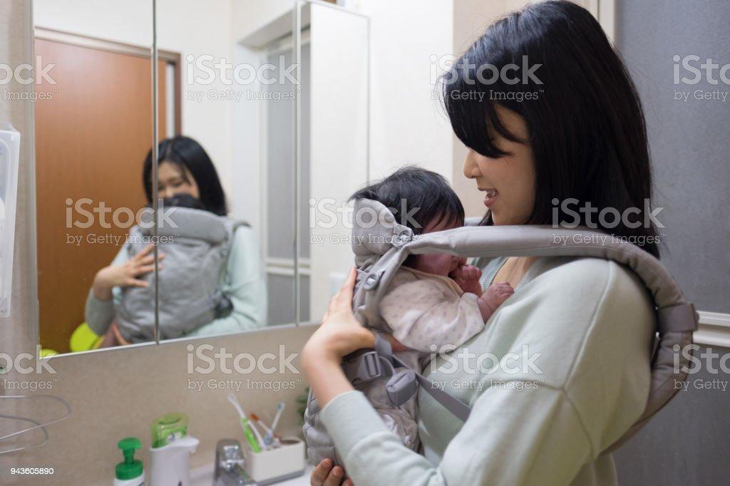 バスルームで赤ちゃんと一緒に鏡を見て母 ストックフォト