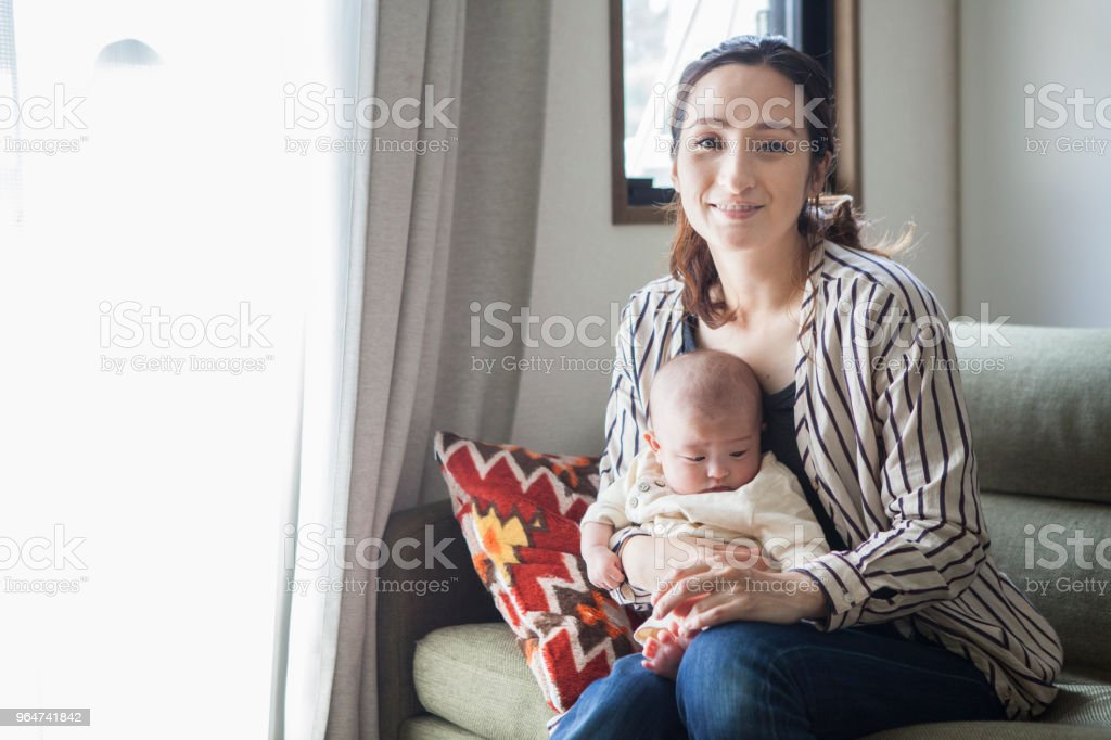 A mother looking at the camera with a baby, and a baby. royalty-free stock photo