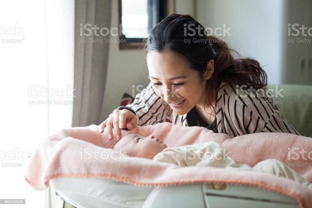 A mother looking into the baby sleeping in the crib. royalty-free stock photo