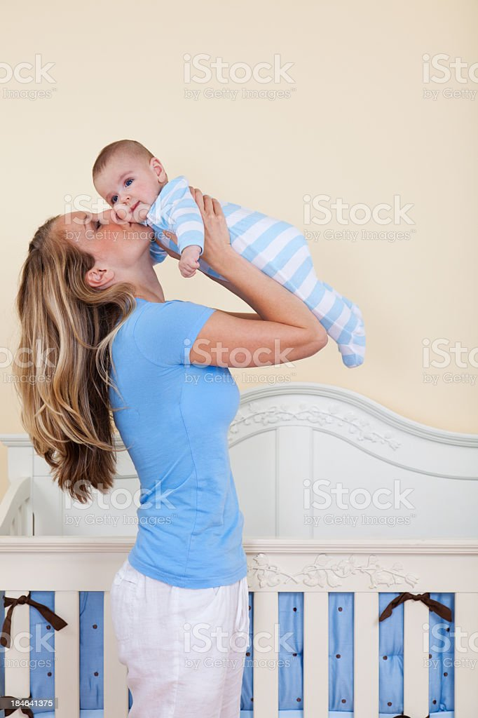 Mother lovingly kissing her baby son near his crib royalty-free stock photo
