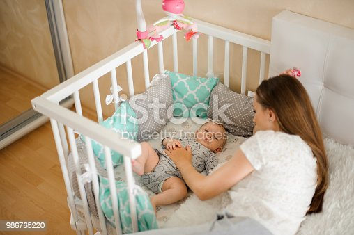 istock Mother lulling cute little newborn baby girl in bed 986765220