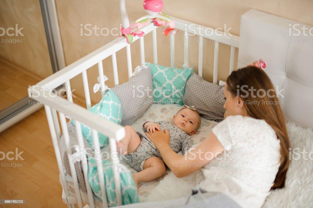 Mutter lulling niedliche kleine neugeborene Mädchen im Bett – Foto