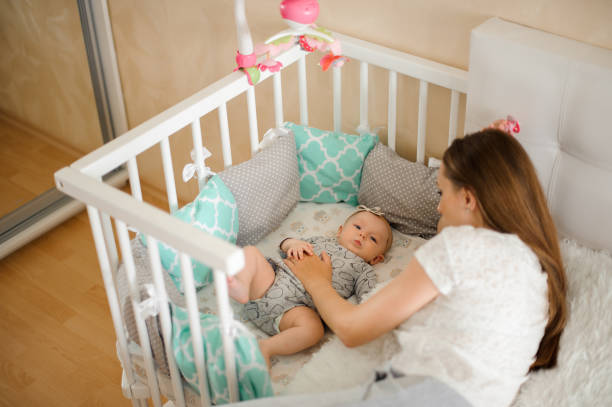 Mother lulling cute little newborn baby girl in bed stock photo