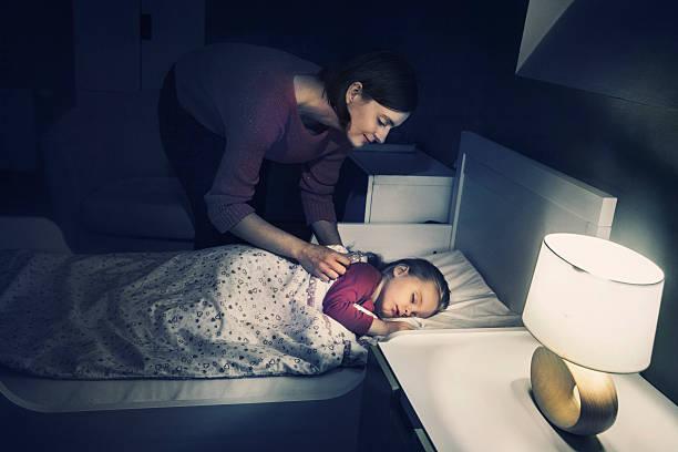 mutter ihre tochter lulling - schlafzimmer beleuchtung stock-fotos und bilder