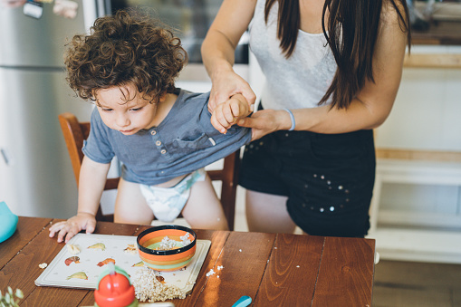 Mother make the mess after toddler lunch