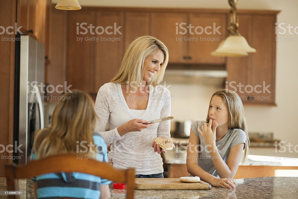 Mother making lunch for girls royalty-free stock photo