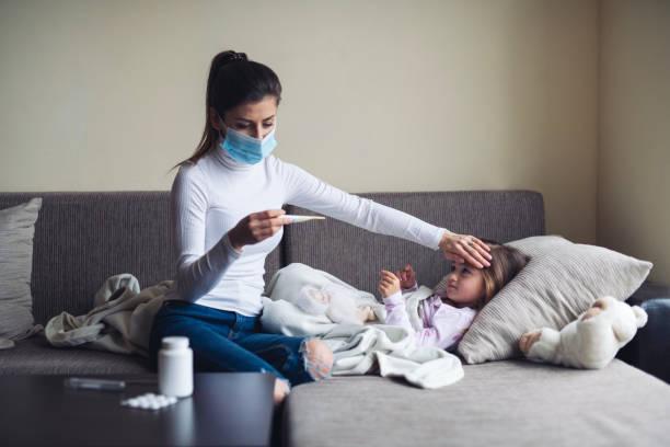 мать измеряет температуру на ее больного ребенка дома. - болезнь стоковые фото и изображения