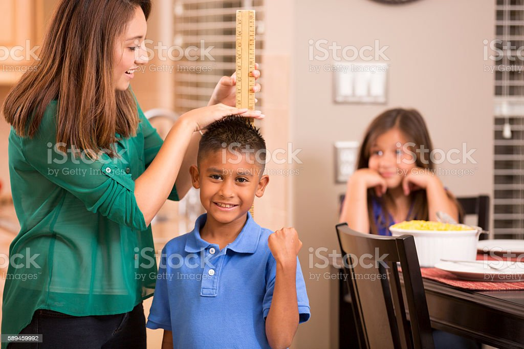 Mother measures growing son's height with yard stick. stock photo