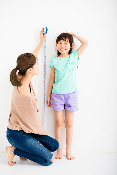 mother measures the growth of her  daughter - height measurement stock photos and pictures
