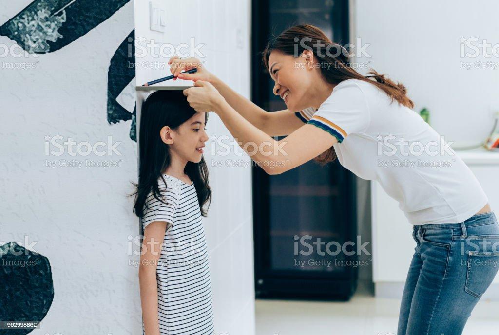 Annesi kızının yükseklik ölçme stok fotoğrafı