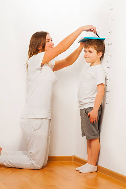 mother measuring her son's height against wall - height measurement stock photos and pictures