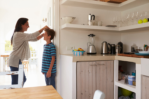 Mother Measuring Son's Height Against Wall