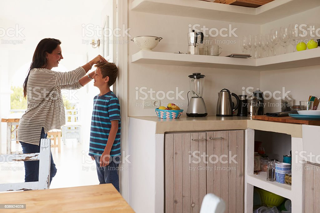 Mother Measuring Son's Height Against Wall stock photo