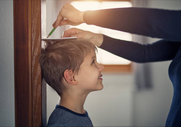 Mother measuring son's height Mother measuring son's height and marking it with pencil on door. Nikon D810 high up stock pictures, royalty-free photos & images