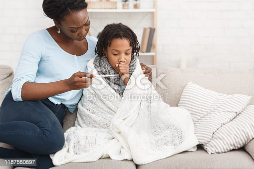 istock Mother measuring temperature of her sick daughter with thermometer 1187580897
