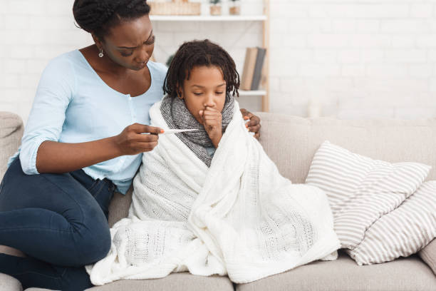 Mother measuring temperature of her sick daughter with thermometer Caring African Mom Checking Temperature Of Her Sick Child At Home, Girl In Blanket flu stock pictures, royalty-free photos & images