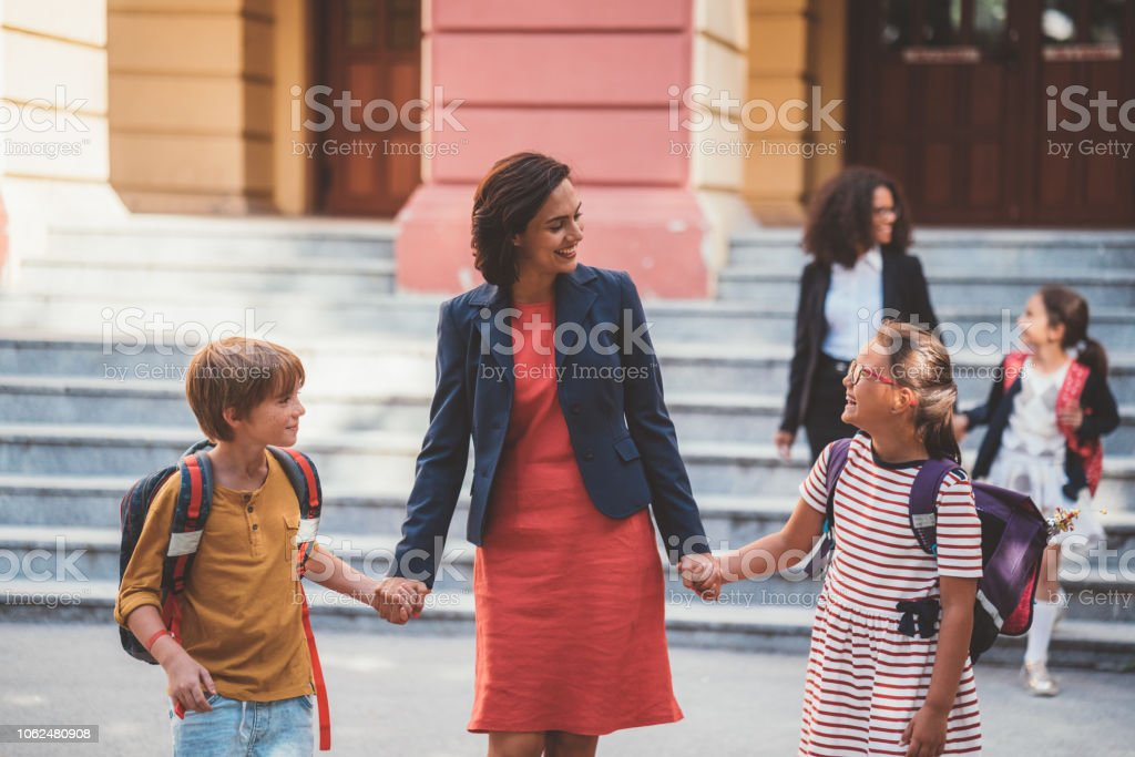 Single mother welcoming her kids after school. Back to school concept...
