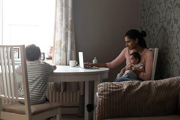 Mother multi-tasking work and children stock photo