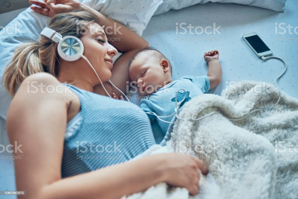 mother napping with her baby stock photo