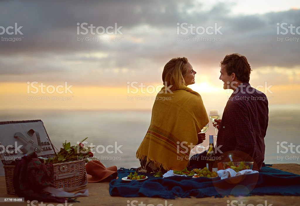 Mother nature setting the scene for love Shot of a young couple enjoying a romantic picnic at sunset 20-29 Years Stock Photo
